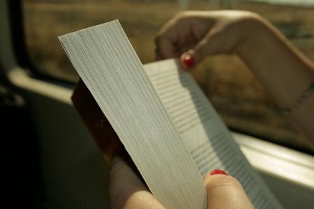 las manos de Cristina leyendo en el tren de Cercanías
